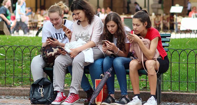 Adolescentes en grupo usando el móvil